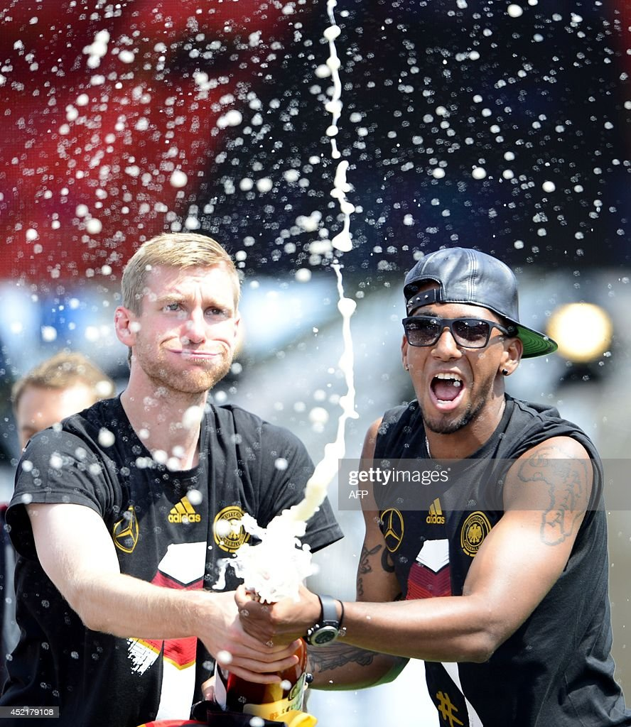 Germany's national football team's defender Per Mertesacker (L) and Germany's defender Jerome Boateng spray sparkling wine as they celebrate their FIFA World Cup 2014 title at a victory parade in front of fans on July 15, 2014 at Berlin's landmark Brandenburg Gate. Germany won their fourth World Cup title, after 1-0 win over Argentina on July 13, 2014 in Rio de Janeiro in the FIFA World Cup Brazil final game. MICHAEL