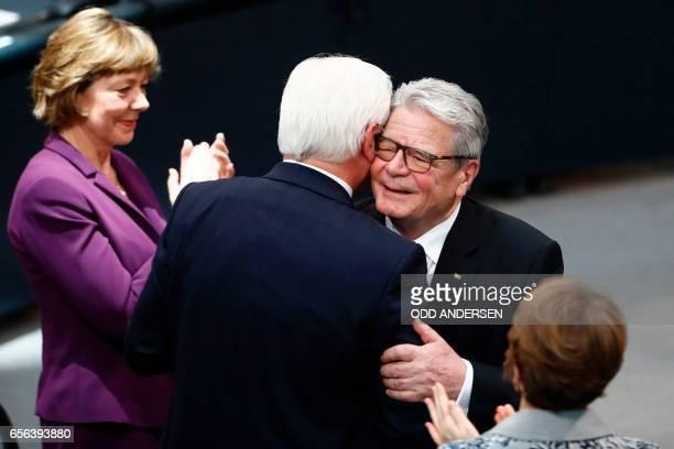 Germany's new President FrankWalter Steinmeier hugs Germany's outgoing President Joachim Gauck as his partner Daniela Schadt applauds during the...