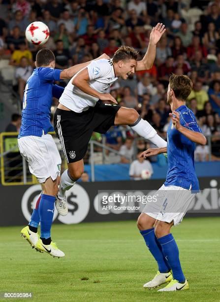 Germany's Niklas Stark and Italy's Mattia Caldara and Daniele Rugani vie for the ball during the UEFA U21 European Championship Group C football...
