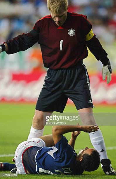 Germany's Oliver Kahn stands over USA's Landon Donovan 21 June 2002 at the Munsu Football Stadium in Ulsan during quarterfinal action between Germany...
