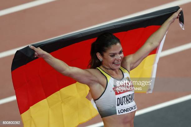 Germany's Pamela Dutkiewicz celebrates with her national flag after finishing first to take bronze in the final of the women's 100m hurdles athletics...