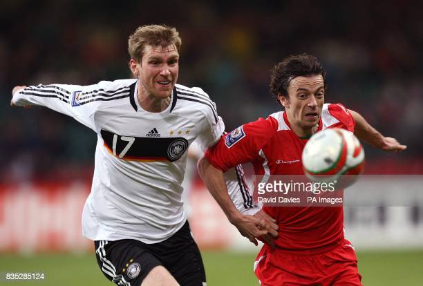 Germany's Per Mertesacker and Wales's Simon Davies battle for the ball