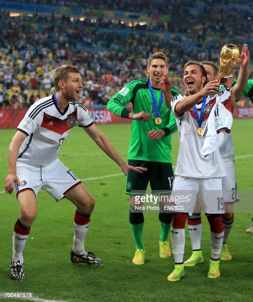 Germany's Per Mertesacker RonRobert Zieler and winning goalscorer Mario Gotze celebrate winning the World Cup final with the trophy