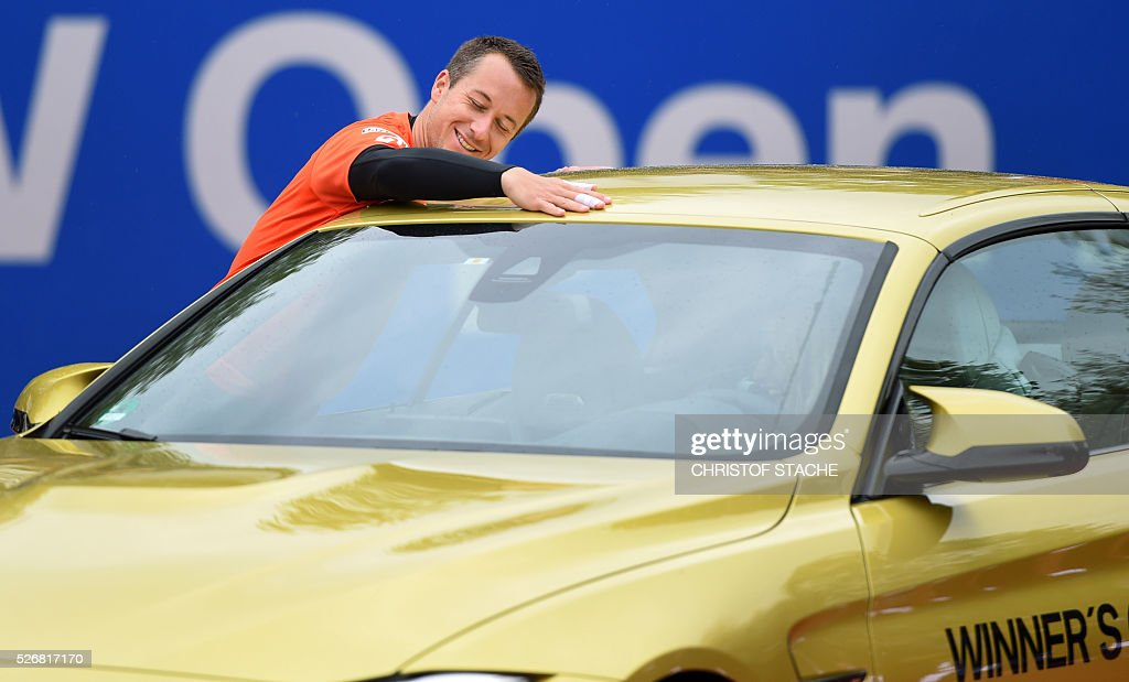 Germany's Philipp Kohlschreiber reacts as he gets the winner's car during the winner ceremony after the final match against Austrian Dominic Thiem at...