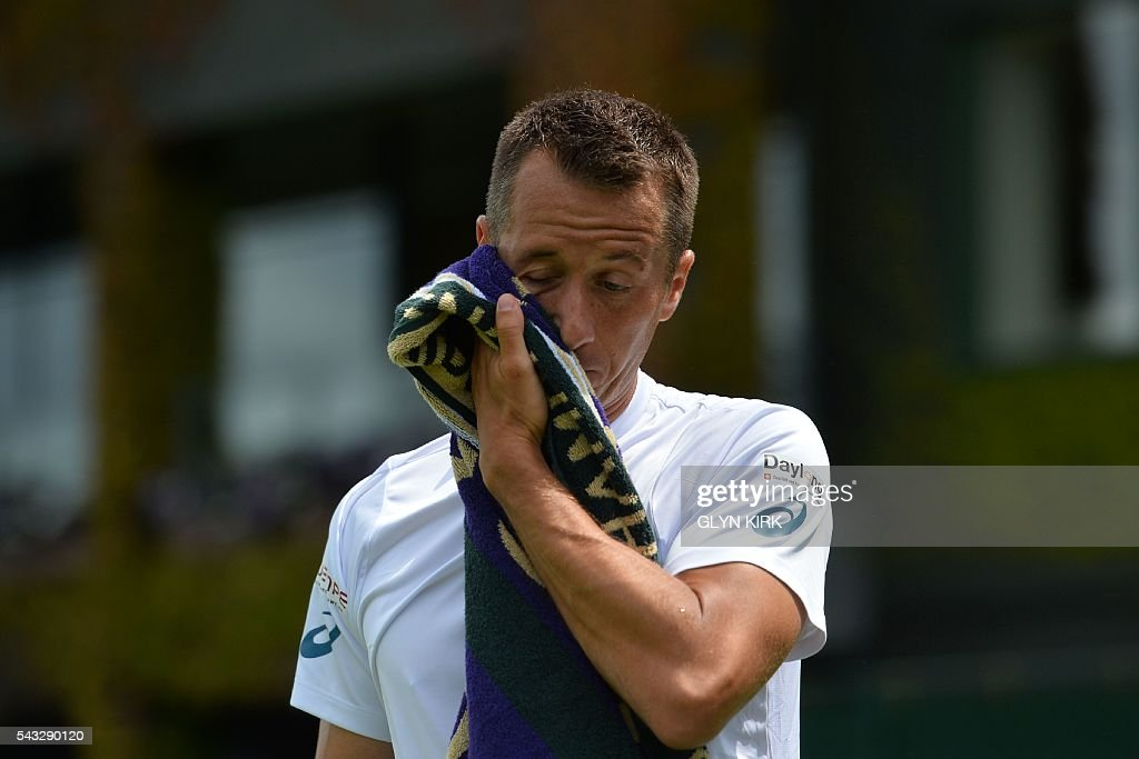 Germany's Philipp Kohlschreiber wipes his face between points against France's Pierre-Hughes Herbert during their men's singles first round match on the first day of the 2016 Wimbledon Championships at The All England Lawn Tennis Club in Wimbledon, southwest London, on June 27, 2016. / AFP / GLYN