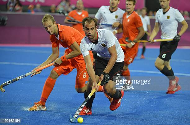 Germany's Philipp Zeller passes the ball in front of The Netherlands' Billy Bakker during the men's field hockey gold medal match Germany vs the...