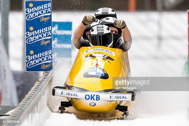 Germany's pilot Nico Walther and his pushers Marko Huebenbecker Christian Poser and Eric Franke react after the final run of the IBSF Bobsleigh...