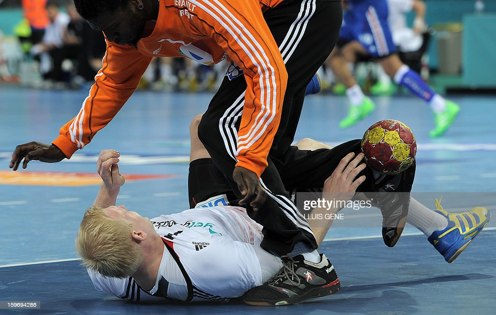 Germany's pivot Patrick Wiencek (down) vies with France's goalkeeper Daouda Karaboue during the 23rd Men's Handball World Championships preliminary round Group A match France vs Germany at the Palau Sant Jordi in Barcelona on January 18, 2013. AFP PHOTO / LLUIS GENE
