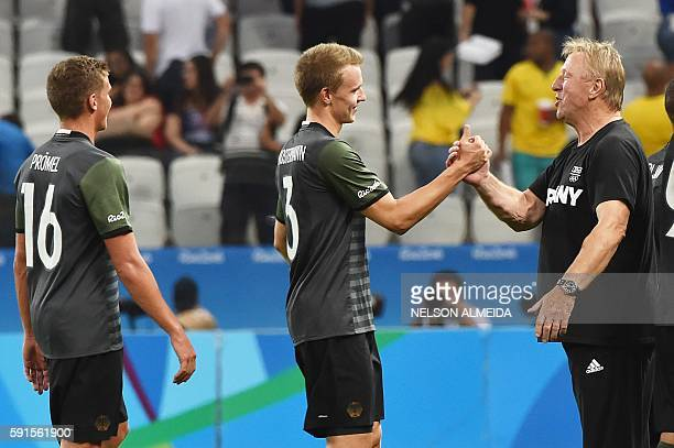 Germany's players Lukas Klostermann and Grischa Proemel celebrates with their coach Horst Hrubesch after defeating Nigeria 20 at the end of their Rio...