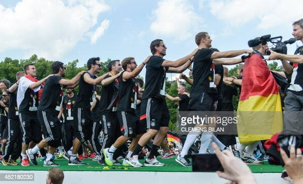 Germany's players perform a conga line during a victory parade of Germany's football national team on July 15 2014 at Berlin's landmark Brandenburg...