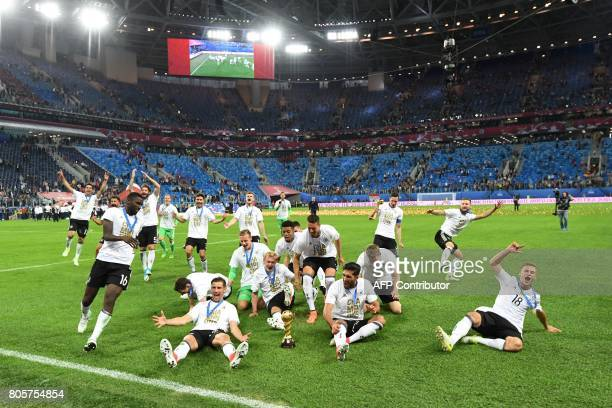 Germany's players run towards the trophy after winning the 2017 Confederations Cup final football match between Chile and Germany at the Saint...