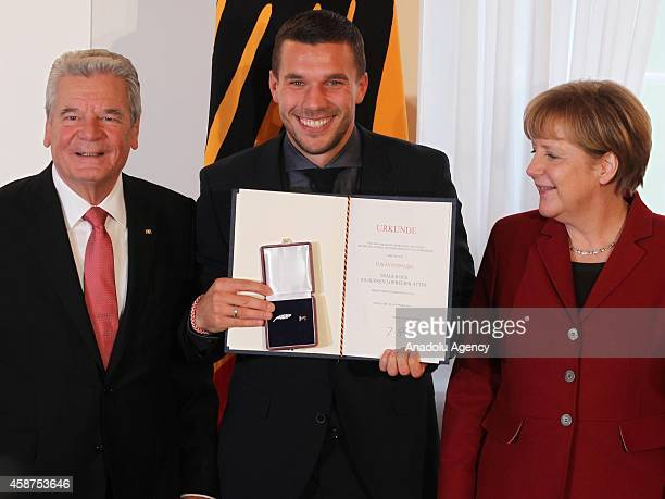 Germany's President Joachim Gauck and German Chancellor Angela Merkel pose with Lucas Podolski during the Silbernes Lorbeerblatt Award Ceremony for...