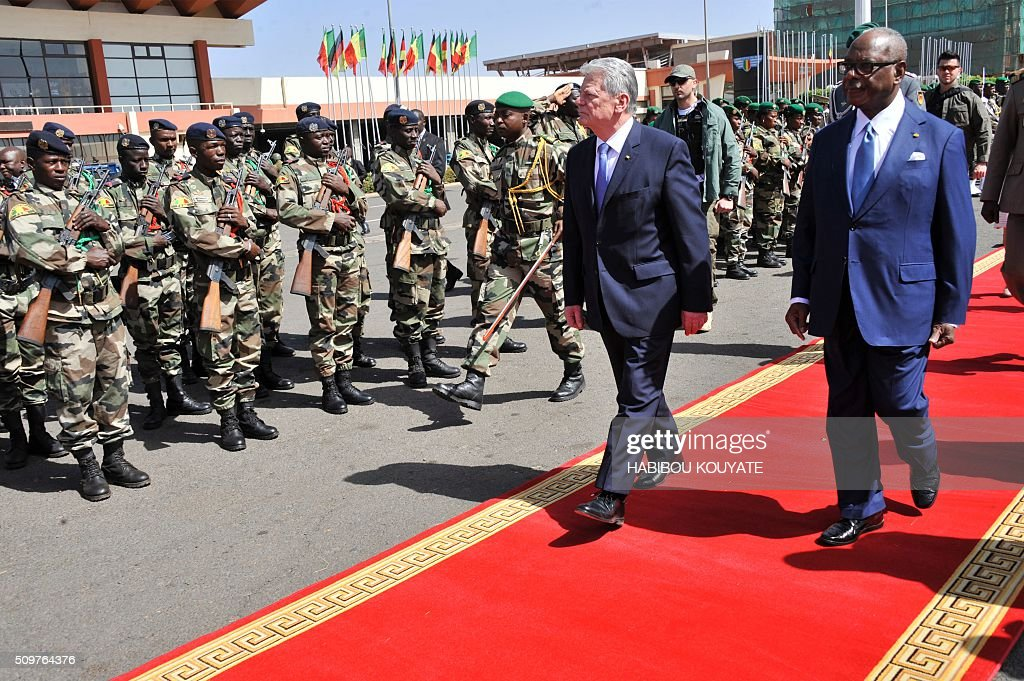 Germany's President Joachim Gauck (L) and his Malian counterpart Ibrahim Boubacar Keita review an honour guard in Bamako on February 12, 2016. Germany heads the military training mission in Mali (EUTM) and will send up to 650 soldiers to Mali, to provide some relief to France in its global fight against the Islamic State jihadists. / AFP / HABIBOU KOUYATE
