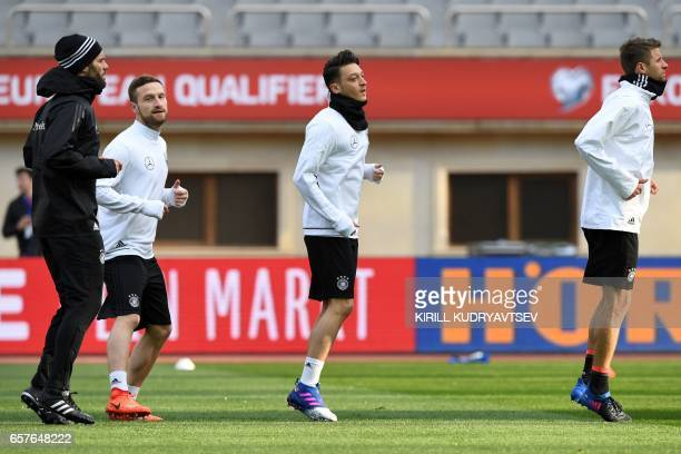 Germany's Shkodran Mustafi Mesut Ozil and Thomas Mueller take part in a training session in Baku on March 25 2017 on the eve of the FIFA World Cup...