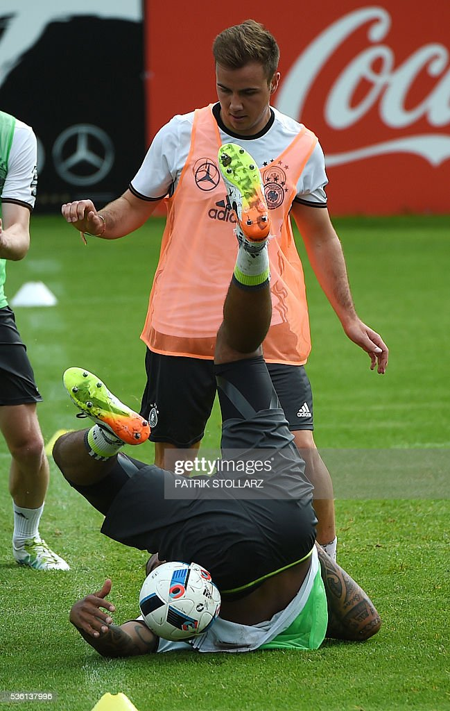 Germany's striker Mario Goetze (top) and Germany's defender Jerome Boateng vie for the ball during a training session on May 31, 2016 in Ascona as part of the team's preparation for the upcoming Euro 2016 European football championships. / AFP / PATRIK