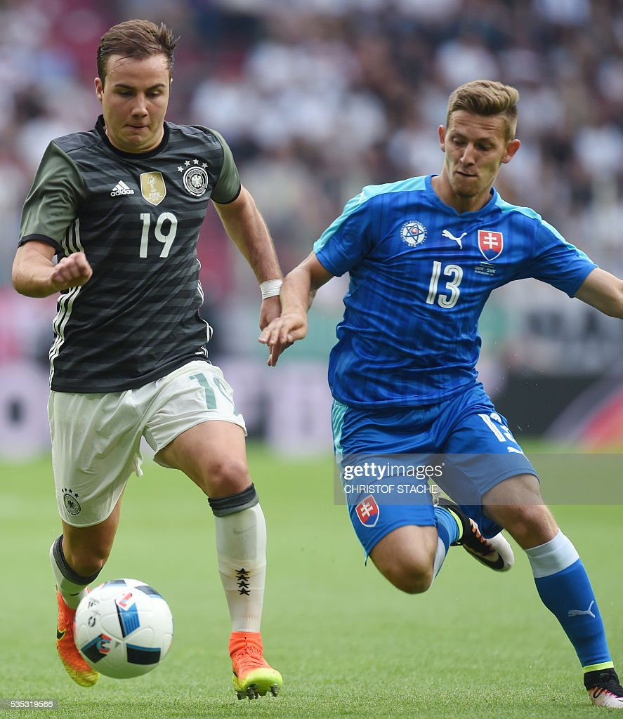Germany's striker Mario Goetze (L) and Slovakian midfielder Patrik Hrosovsky vie for the ball during the friendly football match between Germany and Slovakia in Augsburg, southern Germany, on May 29, 2016. / AFP / CHRISTOF