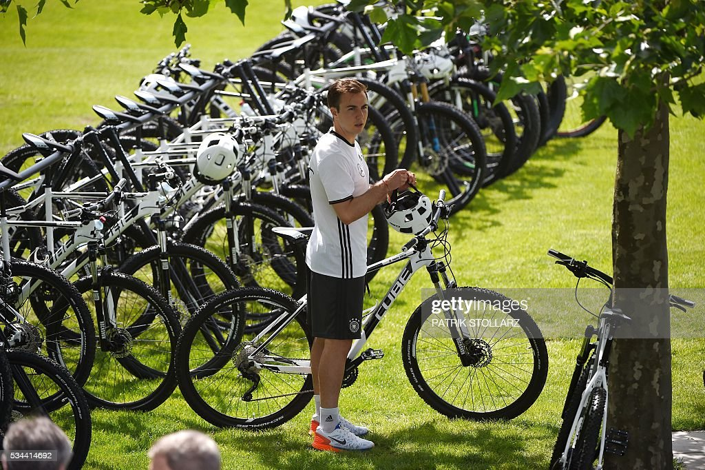 Germany's striker Mario Goetze holds his bike as he prepares to leave the a training session as part of the team's preparation for the upcoming Euro 2016 European football championships, on May 26, 2016 in Ascona. / AFP / PATRIK