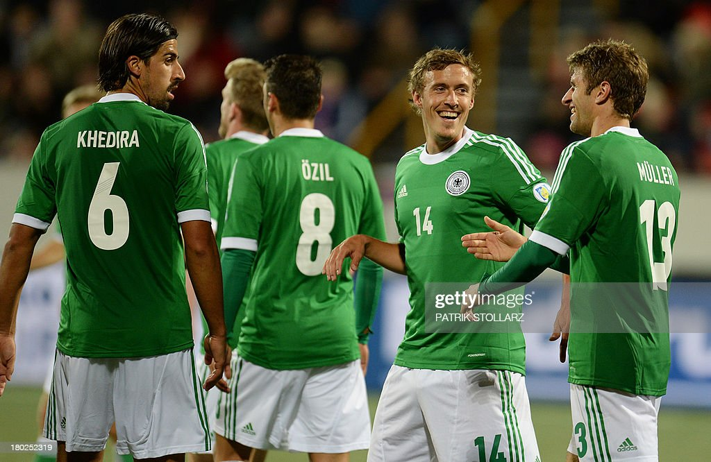 Germany's striker Max Kruse (C) and Germany's midfielder <a gi-track='captionPersonalityLinkClicked' href=/galleries/search?phrase=Thomas+Mueller&family=editorial&specificpeople=5842906 ng-click='$event.stopPropagation()'>Thomas Mueller</a> (R) celebrate during the FIFA World Cup 2014 qualifying football match Faroe Island vs Germany in Torshavn on September 10, 2013.
