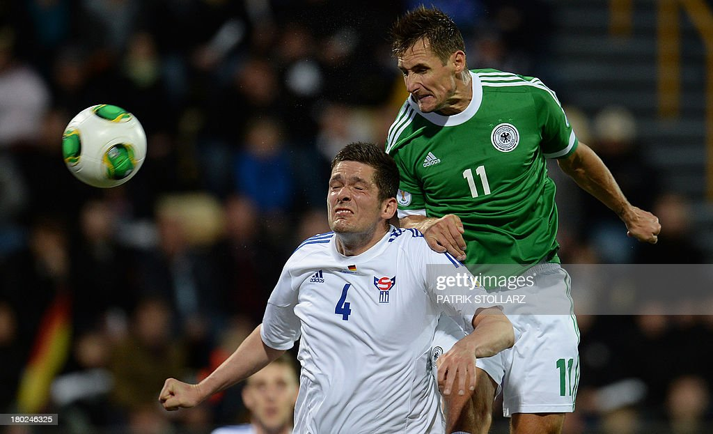 Germany's striker Miroslav Klose (R) and Faroe Island's Attli Gregersen vie for the ball during the FIFA World Cup 2014 qualifying football match Faroe Island vs Germany in Torshavn on September 10, 2013.