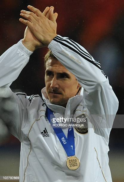 Germany's striker Miroslav Klose applauds after the medal ceremony of the 2010 World Cup third place football match Uruguay vs Germany on July 10...