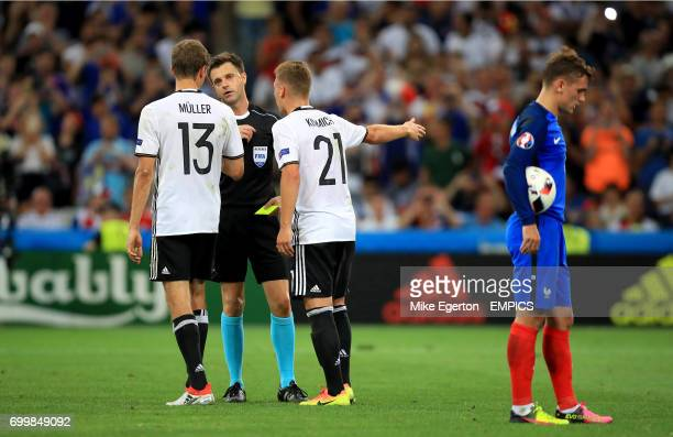 Germany's Thomas Muller and Joshua Kimmich argue with referee Nicola Rizzoli after he awards France a penalty for handball by Bastian Schweinsteiger...