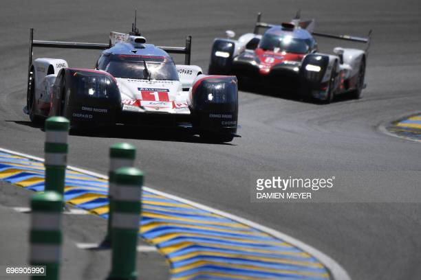 Germanys Timo Bernhard competes on his Porsche 919 Hybrid N°1 ahead of Switzerland's driver Sebastien Buemi on his Toyota TS050 Hybrid N°8 as they...