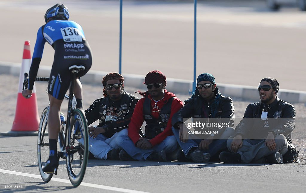 Germany's TNE team's cyclist Andreas Schillinger rides his bike past supporters at the end of the second stage of the 2013 cycling Tour of Qatar, a 14-kilometre team time-trial, in the Qatari capital Doha, on February 4, 2013. BMC won the event in 16min 7.21sec, five seconds ahead of Britain's Team Sky and 10 seconds in front of Omega Pharma, led by former world champion Mark Cavendish.