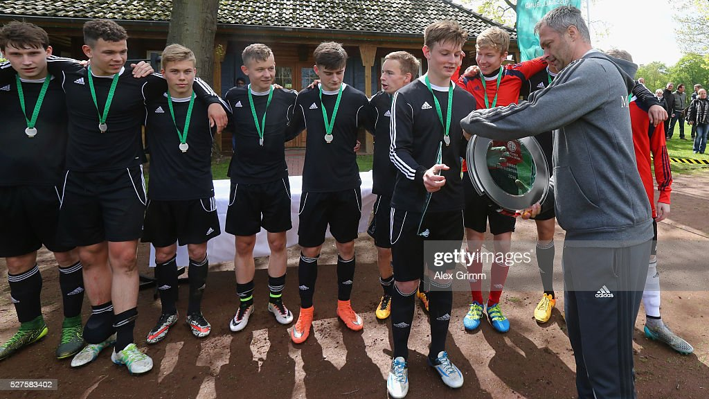 Germany's U16 coach Christian Wueck hands over the trophy to the winning team of Sachsen after the U16 Juniors Federal Cup at Sportschule Wedau on May 03, 2016 in Duisburg, North Rhine-Westphalia.