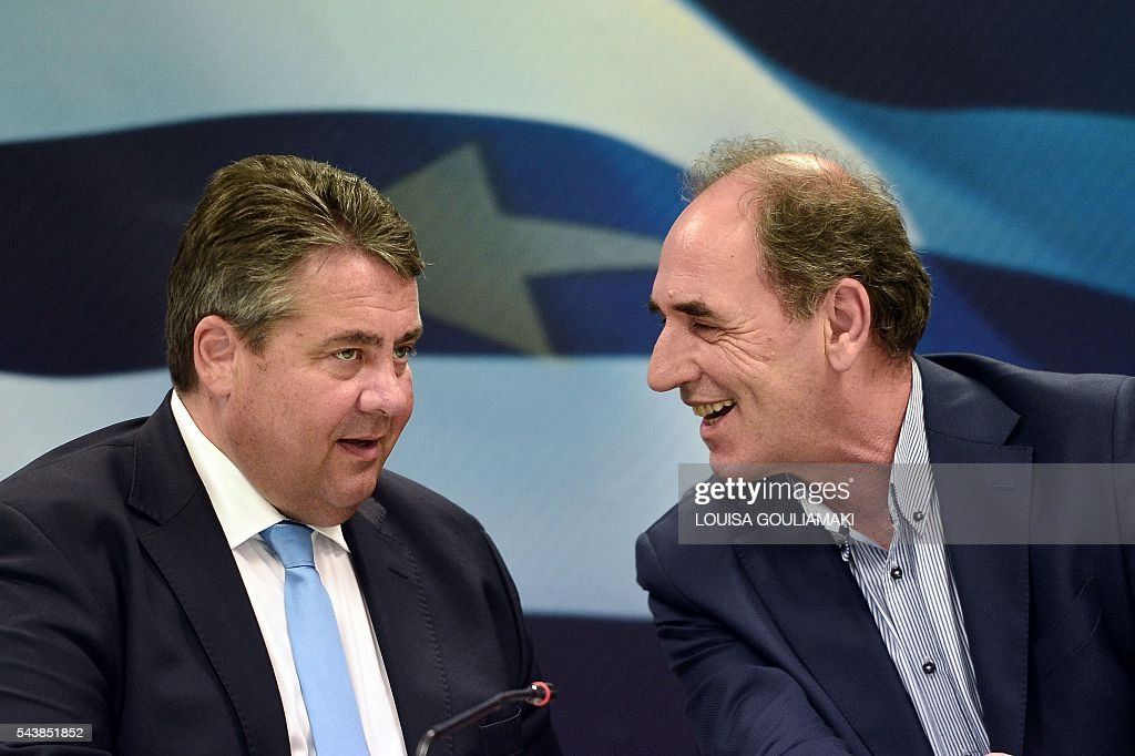Germany's vice chancellor and economy minister Sigmar Gabriel (L) chats with Greek economy minister Giorgos Stathakies at the Greek finance ministry on June 30, 2016. / AFP / LOUISA