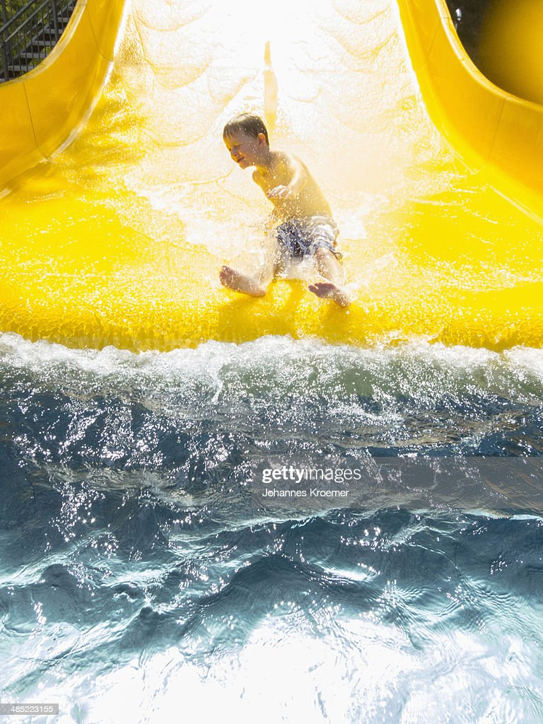 Germany,Thuringia, Boy (6-7) having fun on water slide : Stock Photo