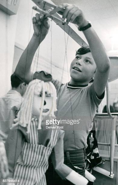 Gerold Rodriguez of 1555 Clay St hangs up the marionettes made from styrofoam He said his teacher made the clothes for the Raggedy Ann She's Mrs...
