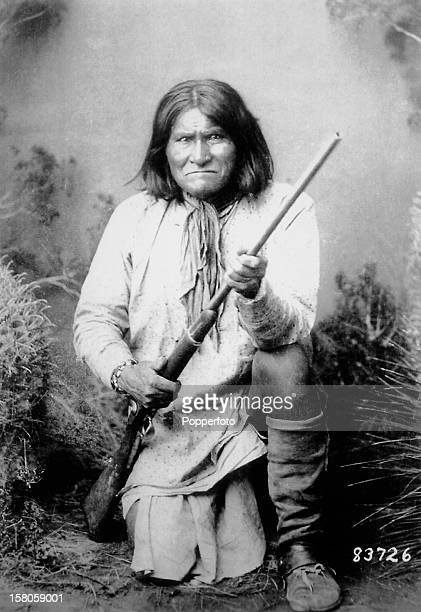 Geronimo leader of the Apache Indian nation in the United States kneeling with his rifle in a studio portrait circa 1887 This image is from the files...