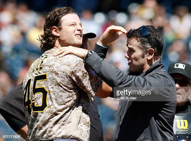 Gerrit Cole of the Pittsburgh Pirates is tended to by athletic trainer Ben Potenziano after being struck in the head by a hit up the middle in the...