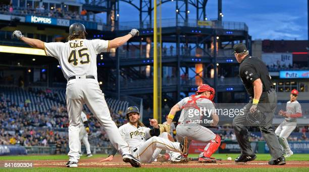 Gerrit Cole of the Pittsburgh Pirates reacts as John Jaso slides safely past Stuart Turner of the Cincinnati Reds to score in the second inning...
