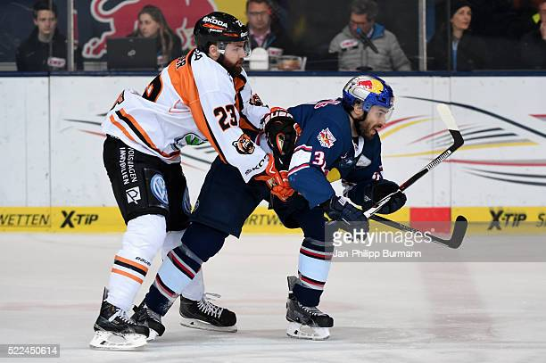 Gerrit Fauser of Grizzlys Wolfsburg and Frederic StDenis of EHC Red Bull Muenchen during the DEL playoff match between the EHC Red Bull Muenchen and...