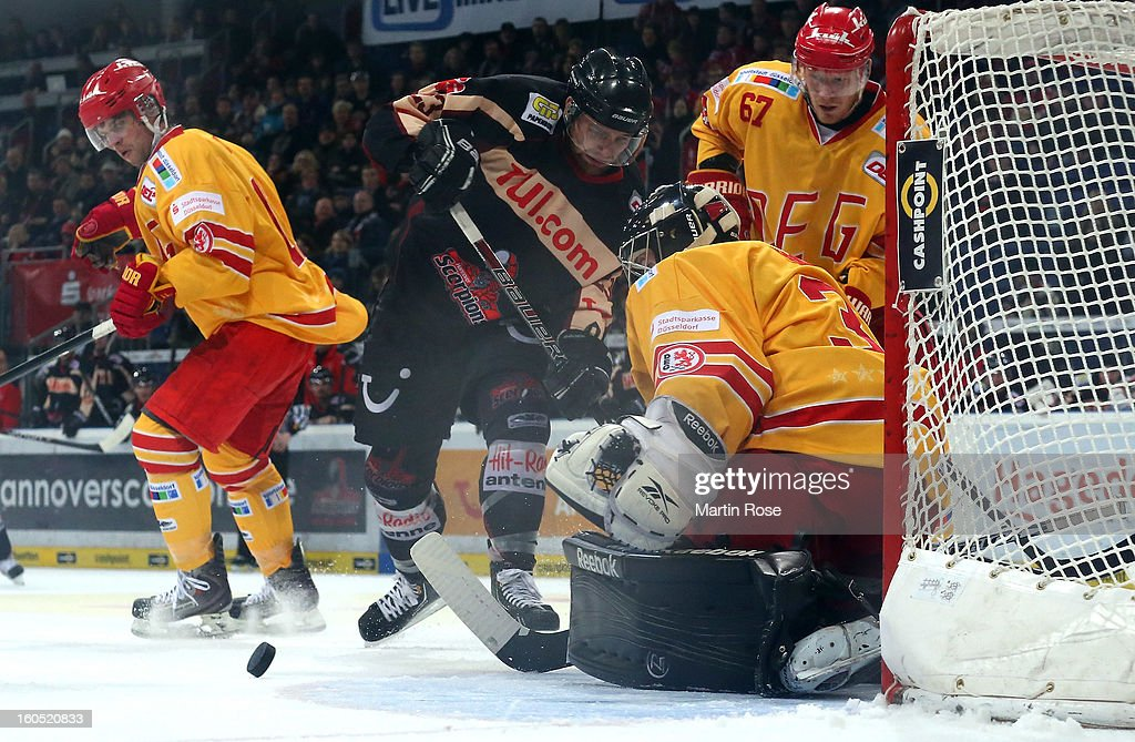 Gerrit Fauser (C) of Hannover fails to score over Felix Bick (R), goaltender of Duesseldorf during the DEL match between Hannover Scorpions and Duesseldorfer EG at TUI Arena on February 1, 2013 in Hanover, Germany.