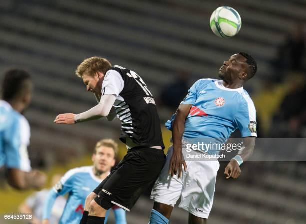 Gerrit Wegkamp of Aalen jumps for a header with EbewaYam Mimbala of Koeln during the third league match between VfR Aalen and Fortuna Koeln on April...