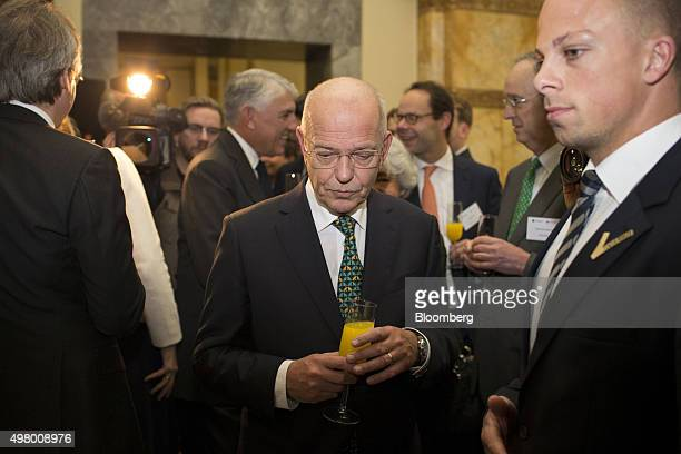 Gerrit Zalm chairman of ABN Amro Group NV center holds a glass of orange juice after opening trading as the Netherland's secondlargest bank makes its...
