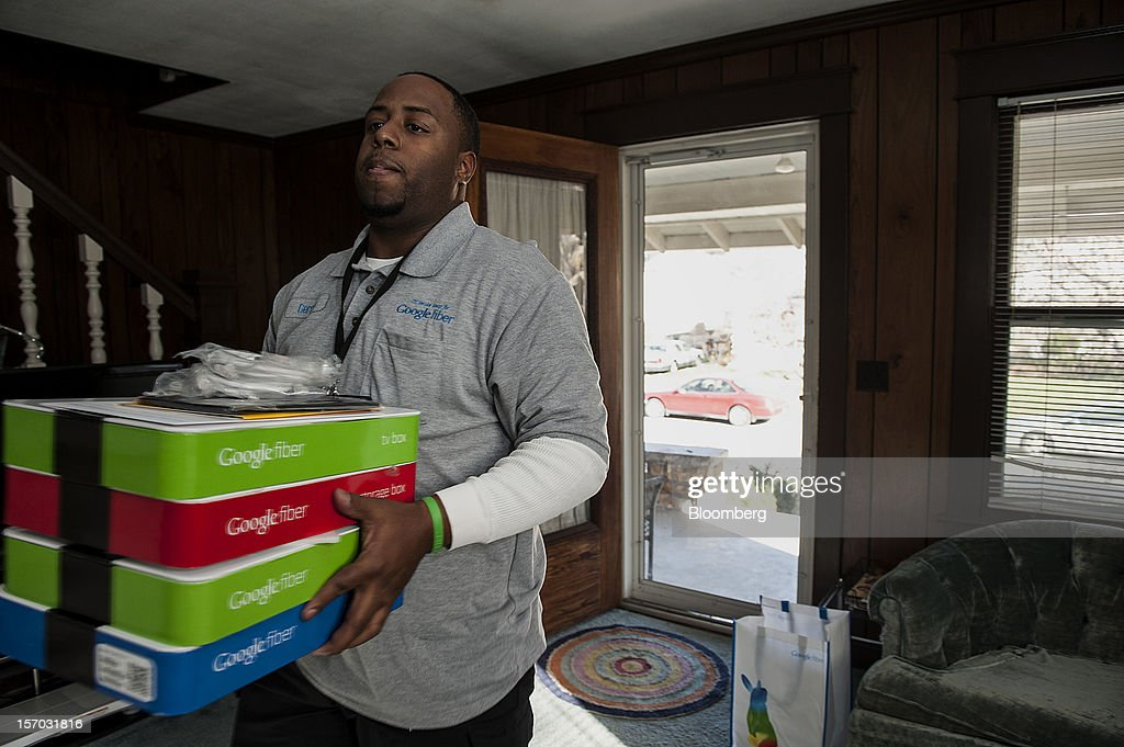 Gerron Diamond, a Google Inc. broadband technician, carries boxes of equipment needed to install Google Fiber network at the home of customer Becki Sherwood in Kansas City, Kansas, U.S., on Tuesday, Nov. 27, 2012. Google Inc. will move a step closer to offering the fastest citywide Internet service in the U.S. when it picks the first neighborhoods in Kansas City to get hooked into a new fiber-optic network. Photographer: Julie Denesha/Bloomberg via Getty Images