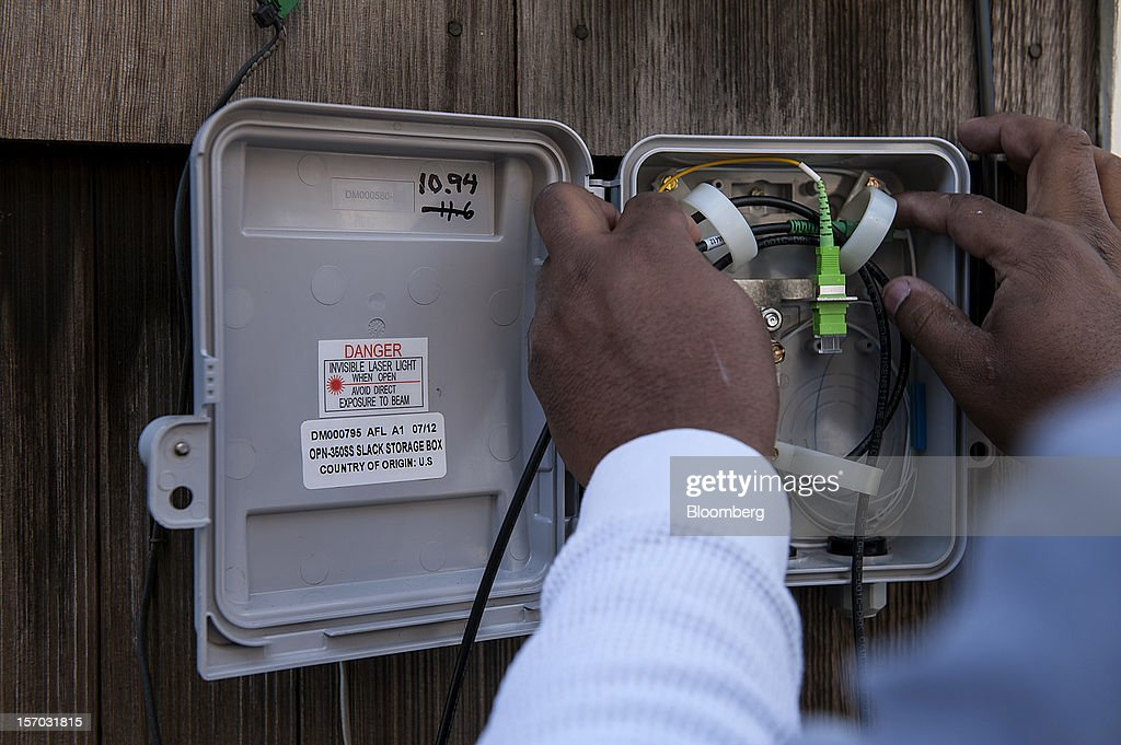 Gerron Diamond, a Google Inc. broadband technician, installs Google Fiber network at the home of customer Becki Sherwood in Kansas City, Kansas, U.S., on Tuesday, Nov. 27, 2012. Google Inc. will move a step closer to offering the fastest citywide Internet service in the U.S. tomorrow when it picks the first neighborhoods in Kansas City to get hooked into a new fiber-optic network. Photographer: Julie Denesha/Bloomberg via Getty Images