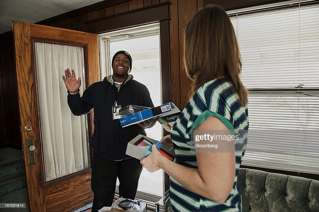 Gerron Diamond, a Google Inc. broadband technician, left, waves while arriving to install Google Fiber network at the home of customer Becki Sherwood in Kansas City, Kansas, U.S., on Tuesday, Nov. 27, 2012. Google Inc. will move a step closer to offering the fastest citywide Internet service in the U.S. tomorrow when it picks the first neighborhoods in Kansas City to get hooked into a new fiber-optic network. Photographer: Julie Denesha/Bloomberg via Getty Images