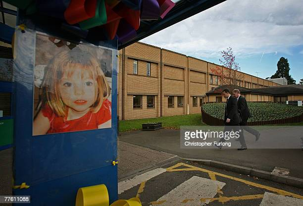 Gerry McCann escorted by his advisor Clarence Mitchell walks past a poster of his missing daughter as he returns to work at Glenfield Hospital where...