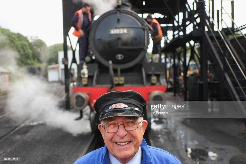 Gerry Skelton poses next to 'Chiru', the locomotive he will drive from Grosmont train engine sheds to a ceremony to mark a second platform opening at Whitby train station on August 15, 2014 in Whitby, England. The second platform will provide passengers with more options for travel to the Yorkshire seaside town on the North Yorkshire Moors Railway and was the first time in half a century two steam locomotives were side by side at the station.