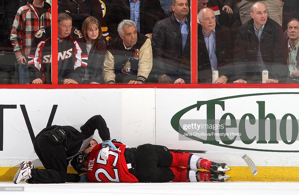 Gerry Townend (L), Head Athletic Trainer of the Ottawa Senators tends to an injured Chris Neil #25 of the Ottawa Senators after he hit the boards hard on a check, during an NHL game against the Boston Bruins, at Scotiabank Place, on March 11, 2013 in Ottawa, Ontario, Canada.