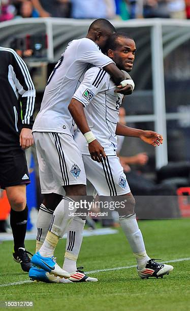 Gershon Koffie of the Vancouver Whitecaps hugs teammate Dane Richards after Richards scored in the second half of the game against Real Salt Lake at...