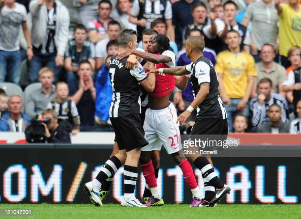 Gervinho of Arsenal confronts Joey Barton of Newcastle shortly before being shown the red card by referee Peter Walton during the Barclays Premier...