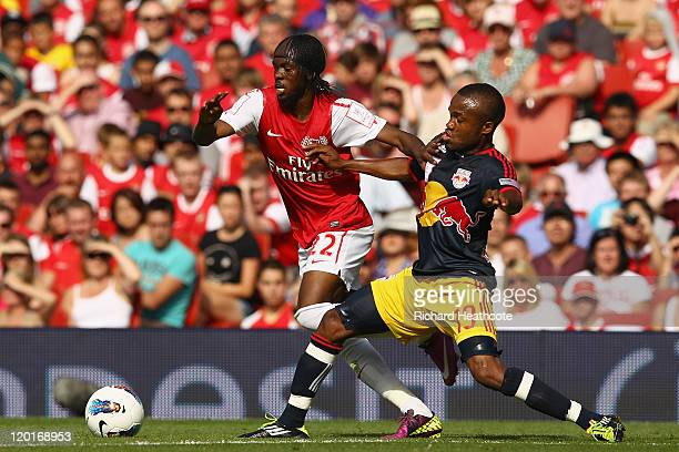 Gervinho of Arsenal holds off the challenge by Dane Richards of New York Red Bulls during the Emirates Cup match between Arsenal and New York Red...