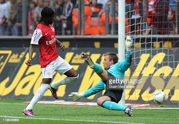 Gervinho of Arsenal shoots past Cologne goalkeeper Michael Rensing to score the second Arsenal goal during the pre season friendly match between...