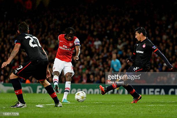 Gervinho of Arsenal shoots past Pablo Contreras of Olympiacos to sxcore the opening goal during the UEFA Champions League Group B match between...