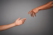 Studio shot of unidentifiable hands reaching for each other against a gray background